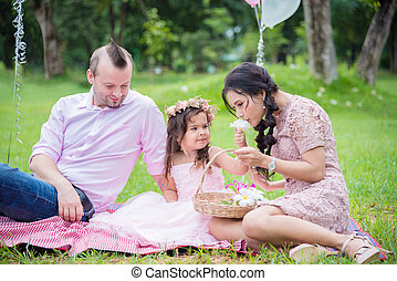 Little cute girl with her parent sitting in park and watching flower in basket