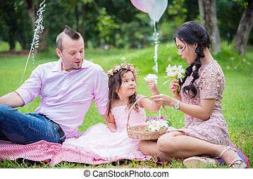 Little cute girl with her parent sittingirl with her parent sitting in park and watching flower in basketg in park and watching flower in basket