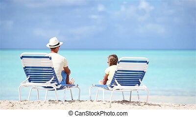 Little cute girl with her young dad sitting on beach enjoy her vacation
