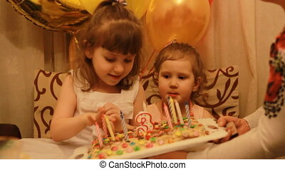 Little cute girls and on birthday dessert at party. Funny happy kids. The concept of a children's holiday. 3 years.