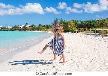 Little cute girls walking along the white beach and having fun