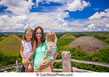 Little cute girls with their mother on a background of the Chocolate Hills in Bohol