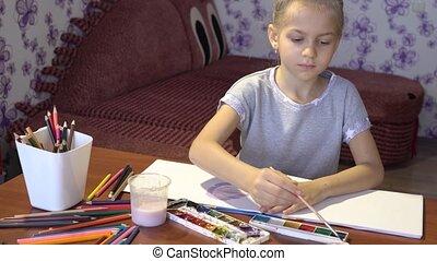 Little cute light girl paints in an album in her room....