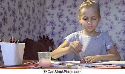 Little cute light girl paints in an album in her room