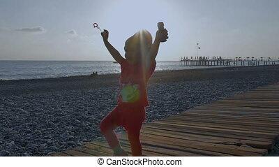 Little cute little girl blows soap bubbles on the beach