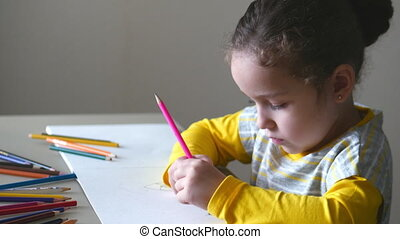 Little cute little girl draws her house with colored pencils. 4K.