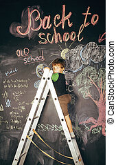 little cute real boy at blackboard in classroom, back to school close up