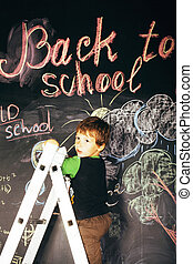 little cute real boy at blackboard in classroom, back to school concept