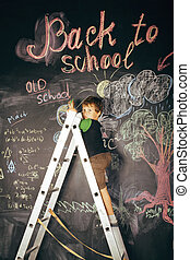 little cute real boy at blackboard in classroom, back to school