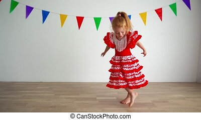Little cute redhead girl dancing in bright light living room at home