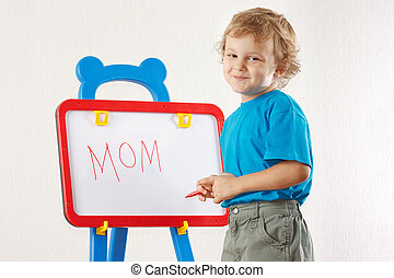 Little cute smiling boy wrote the word mom on whiteboard