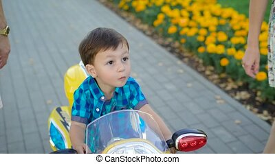 little dark-haired boy is riding toy motorcycle in park in summer day near his mother and father