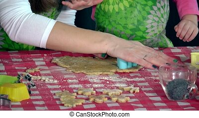Little daughter and mother hands making cookies with colorful forms