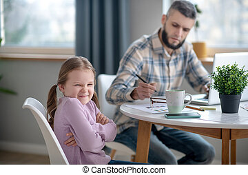 Little daughter and young dad sitting at the table at home.
