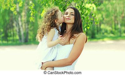 Little daughter child kissing her loving mom in a summer park