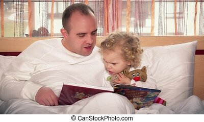 Little daughter girl sitting on bed with father and reading book