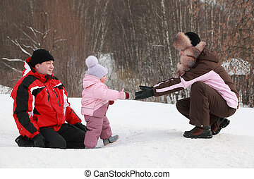 little daughter goes from father to mother at snow in winter, focus on girl