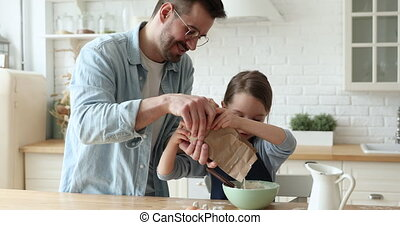 Little daughter helping father making dough for pancakes in kitchen