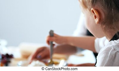 Little daughter helps her mother for cooking cottage cheese...