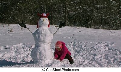 little daughter make a snowman in the meadow near the forest.