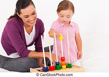 little daughter playing educational toy
