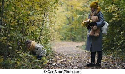Little daughter with her mommy walking in autumn park - plays and hides behind the leaves