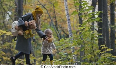 Little daughter with her mommy walks in autumn park - plays the leaves