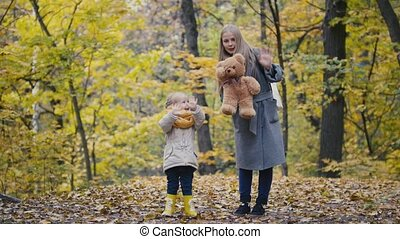 Little daughter with her mother and Teddy Bear walking in autumn park - waving hands at the camera