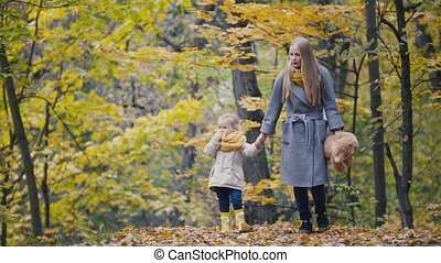 Little daughter with her mother and Teddy Bear walking in autumn park