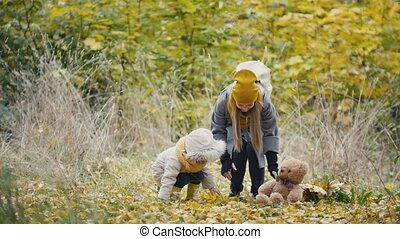 Little daughter with her mother plays with yellow leaves in autumn park