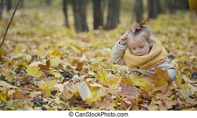 Little daughter with her mother plays with yellow leaves in autumn park - the girl is happy and laughing
