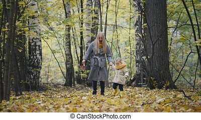 Little daughter with her mother walk in the autumn woods and...