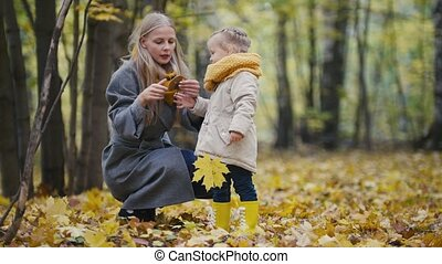 Little daughter with her mother walking in autumn forest - mom shows daughter mushroom