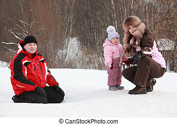 little daughter with mother, father sitting at snow in winter, focus on girl