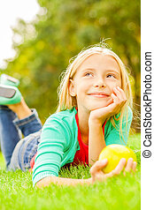 Little day dreamer. Cute little girl leaning head on hand and looking away with smile while lying on the green grass
