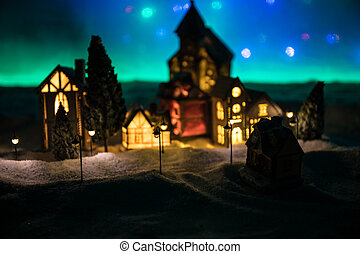 New Year miniature house in the snow at night with fir tree.