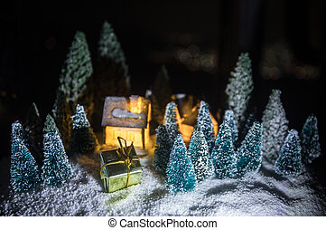New Year miniature house in the snow at night with fir tree. Holiday concept. Selective focus