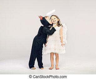 Little devil-boy kissing his angel friend
