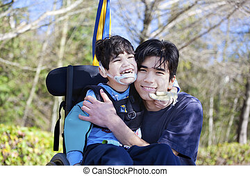 Little disabled boy in wheelchair hugging older brother...