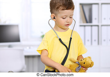 Little doctor examining a  toy bear  patient by stethoscope