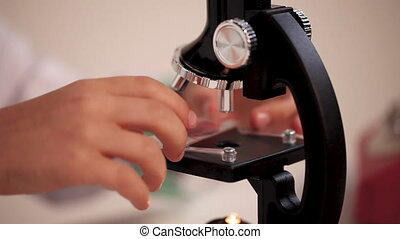 little doctor puts a slide with a blood sample under the microscope