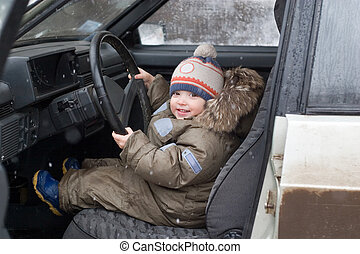 cute little boy sitting in the car at the driver place, looking into the camera and smiling