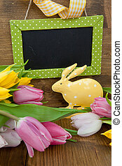 Little Easter bunny and colorful tulips