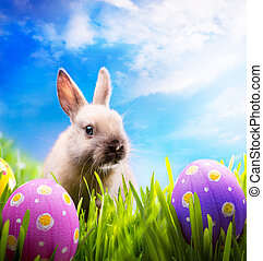 Little Easter bunny and Easter eggs on green grass - art...