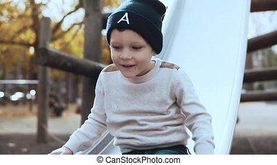 Little European boy going down a park slide. Happy carefree...