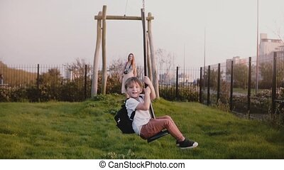Little European boy on a city park zipline. Excited happy male kid rides long zip wire smiling. Front view. Childhood.