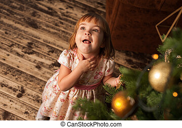 Little excited girl decorating Christmas tree