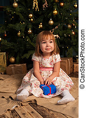 Little excited girl sitting near Christmas tree