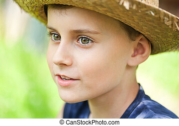 Close up portrait of a country boy with a straw hat