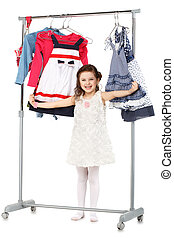 Little fashionable girl chooses clothes in a wardrobe